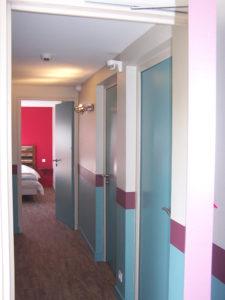 """Hotel """"Les Remparts"""" de Belle île. Couloirs et au fond chambre framboise"""
