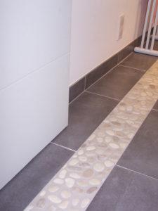 Insertion des galets du bac à douche dans le carrelage de la salle de bain