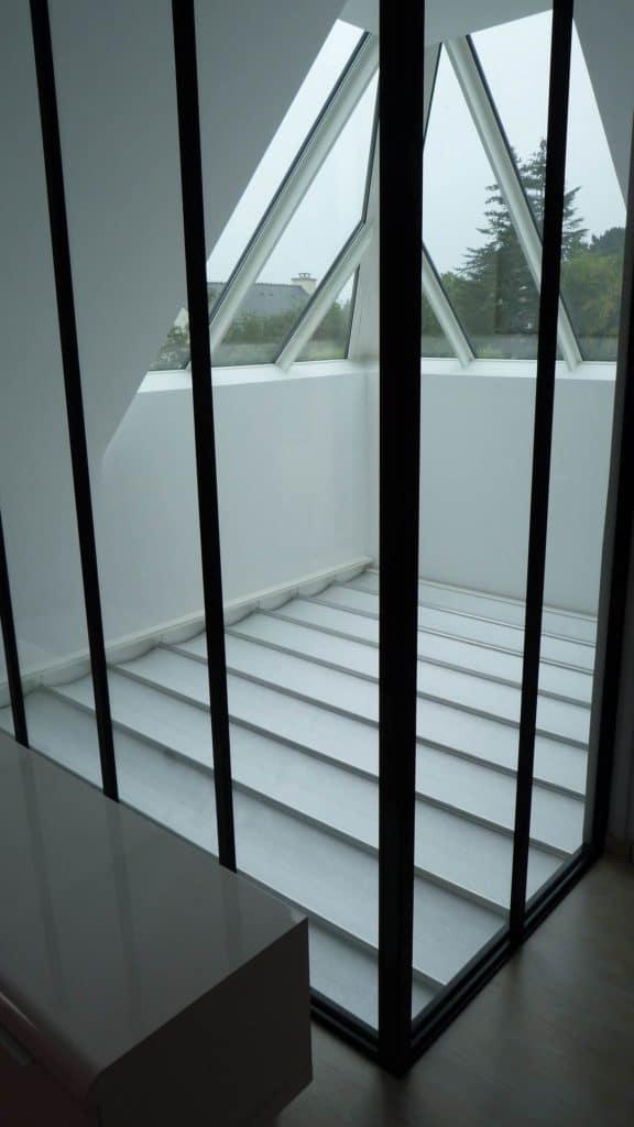 Mezzanine fermée par verrière avec store déroulé pour éviter la chaleur.